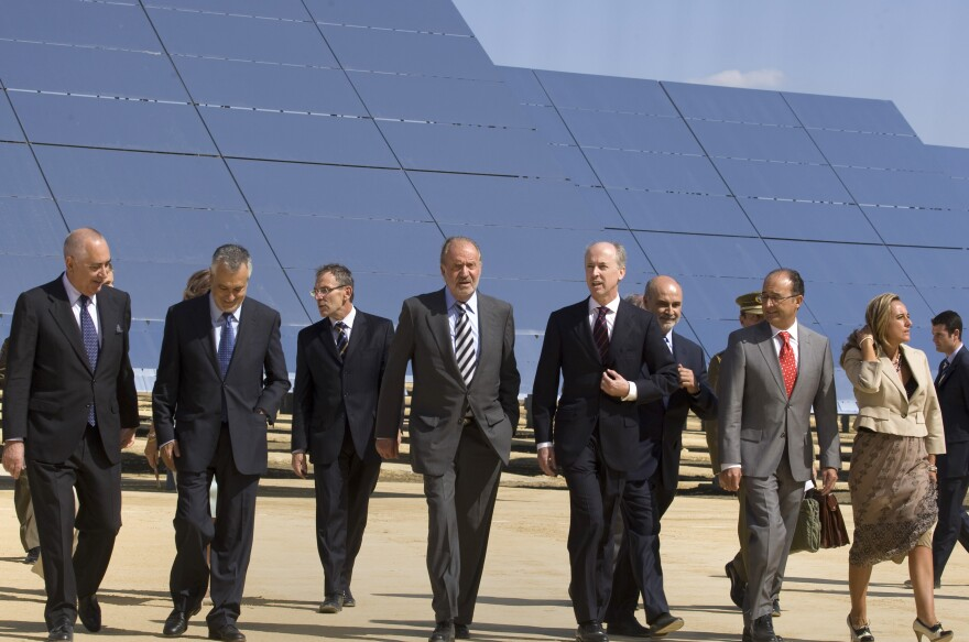 Spain's former king, Juan Carlos (fourth from left), walks with Abengoa Chairman Felipe Benjumea (to the right of the king), in front of a new solar tower in southern Spain in 2009. Abengoa, a large international company focused on renewable energy, now faces potential bankruptcy.