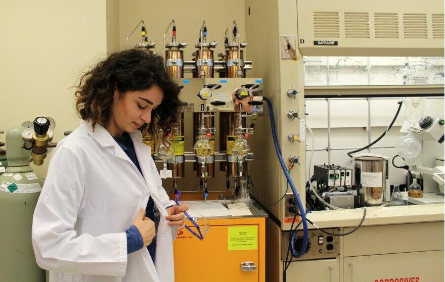 Ranad Humeidi buttons her lab coat and puts on protective glasses to explain the instruments used to study chemicals behind her.