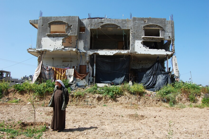 Hassan Faraj in the backyard of his damaged home in Gaza City. The 11 family members moved back in four months ago, though it's still not clear when the family will receive money to repair the damage.