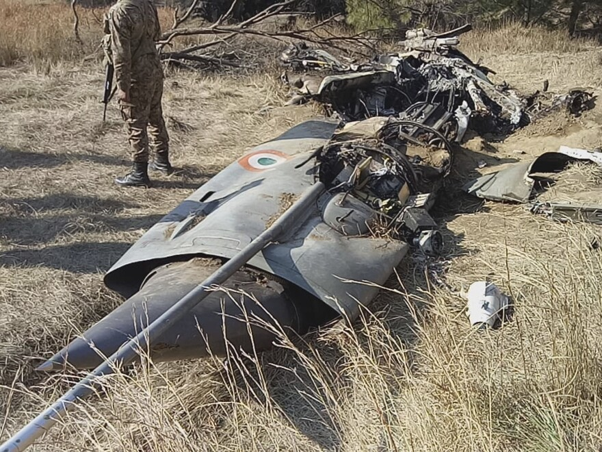 A Pakistani soldier stands guard near the wreckage of an Indian plane shot down by the Pakistan military on Wednesday, in Hurran, near the Line of Control in Pakistani Kashmir, on Thursday.