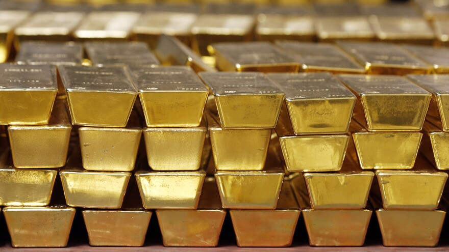 Gold bars are stacked in a vault at the United States Mint, in West Point, N.Y., in 2014. The settlement price for gold futures reached a record high of $1,931 per ounce Monday — and many analysts predict the price will head even higher.