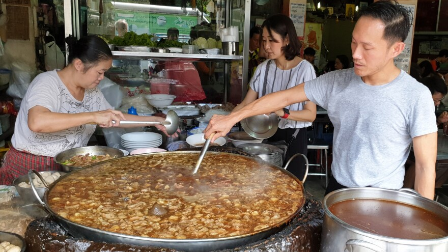 Nattapong Kaweeantawong, a third-generation owner of Wattana Panich, stirs the soup while his mother (left) helps serve and his wife (center) does other jobs at the restaurant. Nattapong or another family member must constantly stir the thick brew.