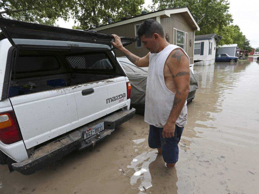 San Marcos, Texas, resident Keith Varela checks out the damage done to his wife's truck in the San Marcos Mobile Home Park on Sunday.