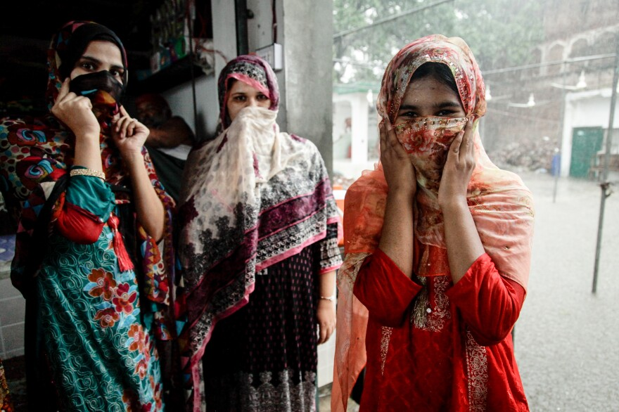 Aya (right), 19, partially covers her face as she poses alongside her sister Sania, 22, and their mother. They visited a shrine in Lahore with their family patriarch Abdul Aziz, who remembers tending fields alongside Hindus before British-ruled India was partitioned.