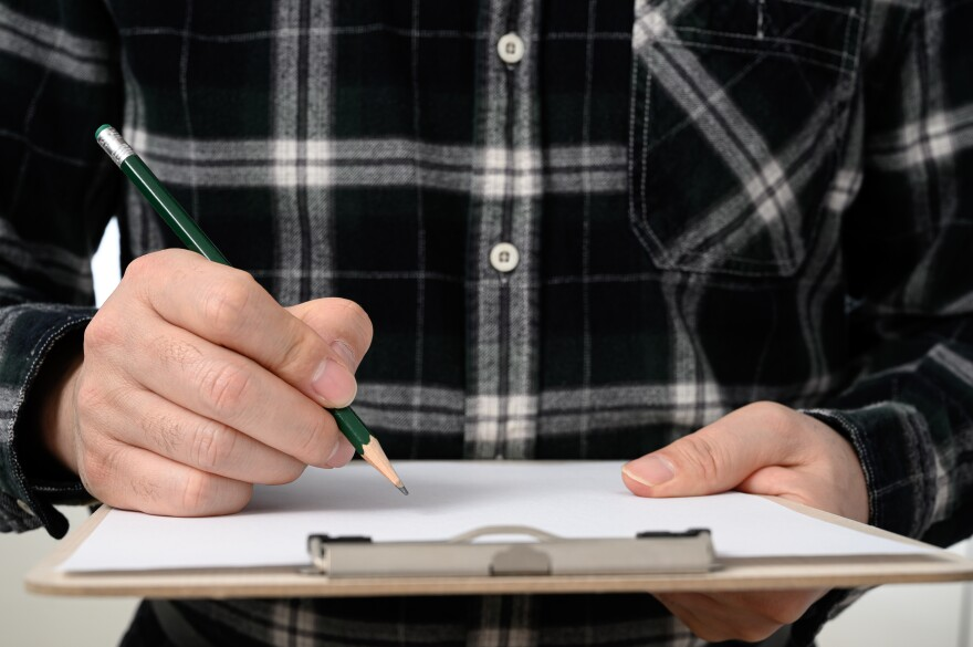 Photo of man signing a piece of paper on a clipboard.