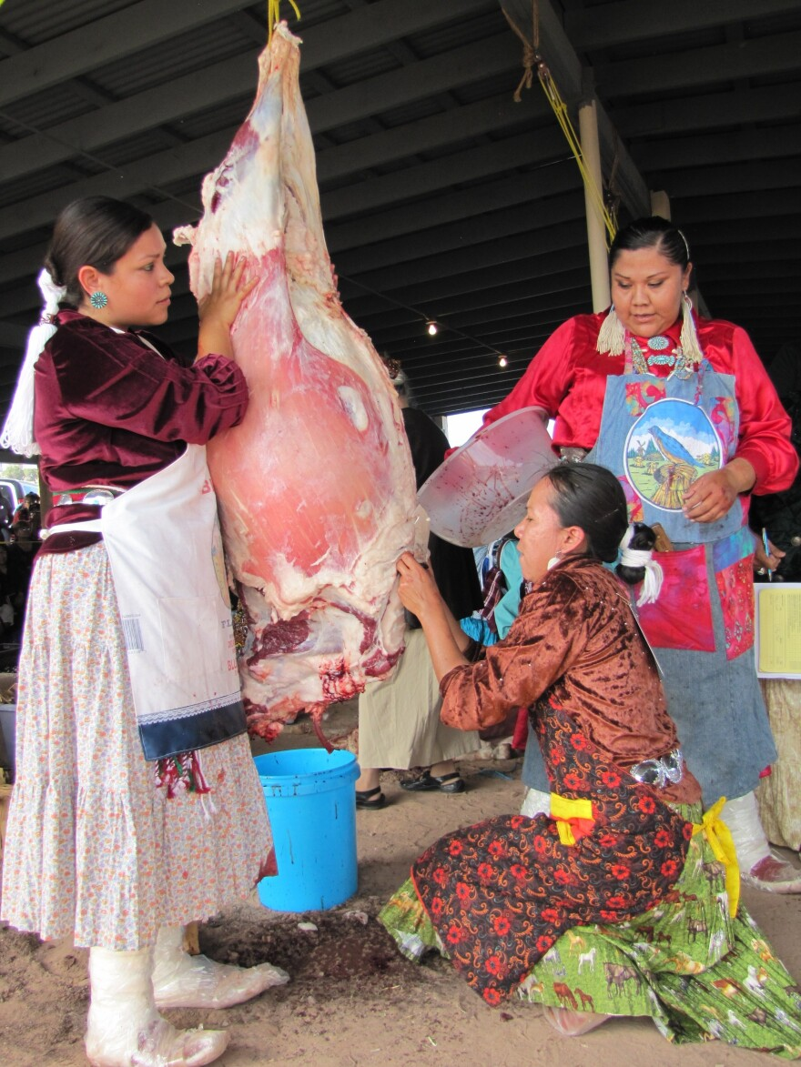 """Miss Navajo contestants must work in teams to butcher sheep. From left, Krystal Parkhurst, Leandra """"Abby"""" Thomas and Charlene Goodluck had to cut the sheep's throat, remove the stomach and quarter the carcass."""