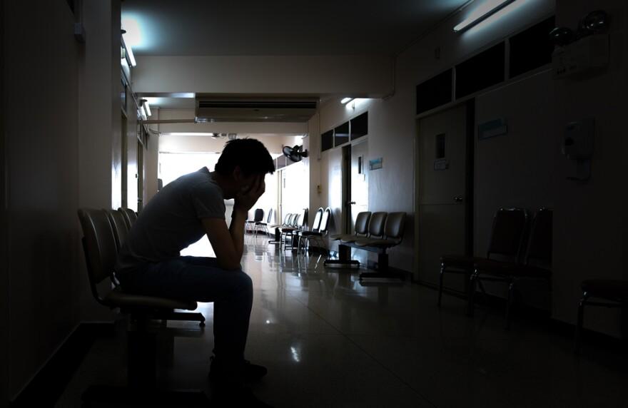 Man sitting in hospital corridor worried