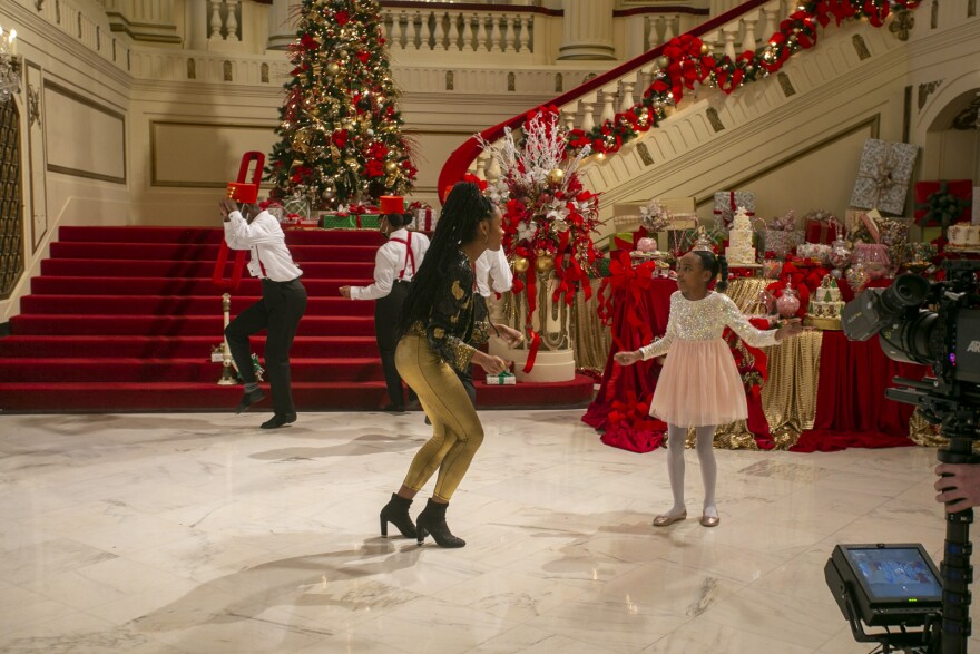 """Kennedy Holmes (center left) and Riley Adams (center right) act out a scene filmed inside Powell Hall for """"A New Holiday."""""""