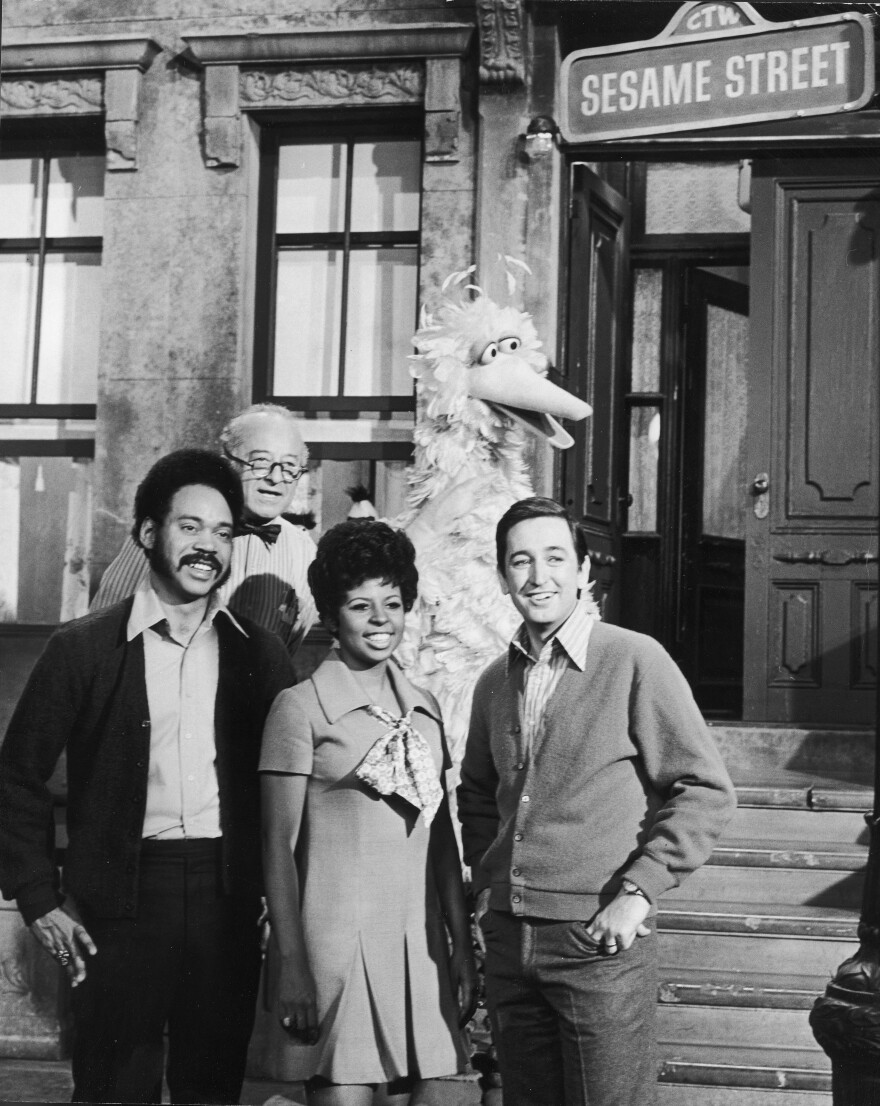 A <em>Sesame Street</em> promotional still from 1969 shows actors Matt Robinson, Will Lee, Loretta Long and Bob McGrath on set. Also Big Bird.