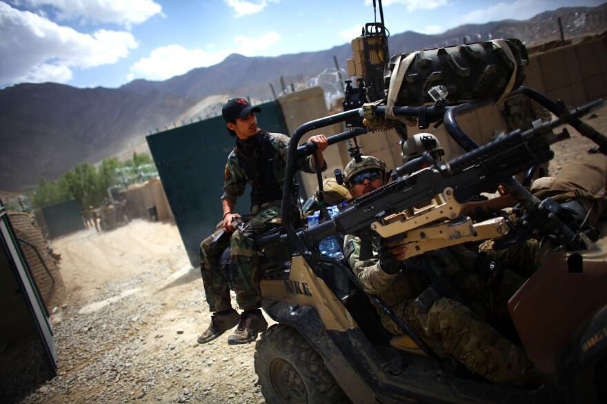 An Afghan soldier rides on the back of a U.S. Green Beret vehicle near the village of Kasan, west of Kabul, in 2013. American combat forces will leave by year's end, but it's not clear how the Afghan forces will handle the Taliban threat.