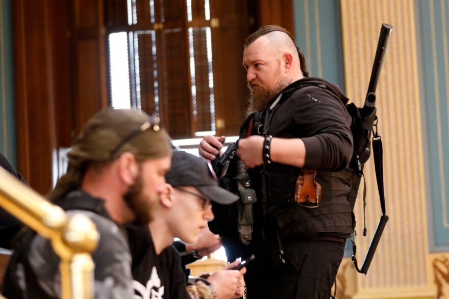 William Null (R) stands in the gallery of the Michigan Senate Chamber during the American Patriot Rally on the steps of the Michigan State Capitol in Lansing, Michigan. Others are unidentified. The Nulls were charged for their alleged roles in the plot to kidnap Gov. Gretchen Whitmer, according to the FBI.
