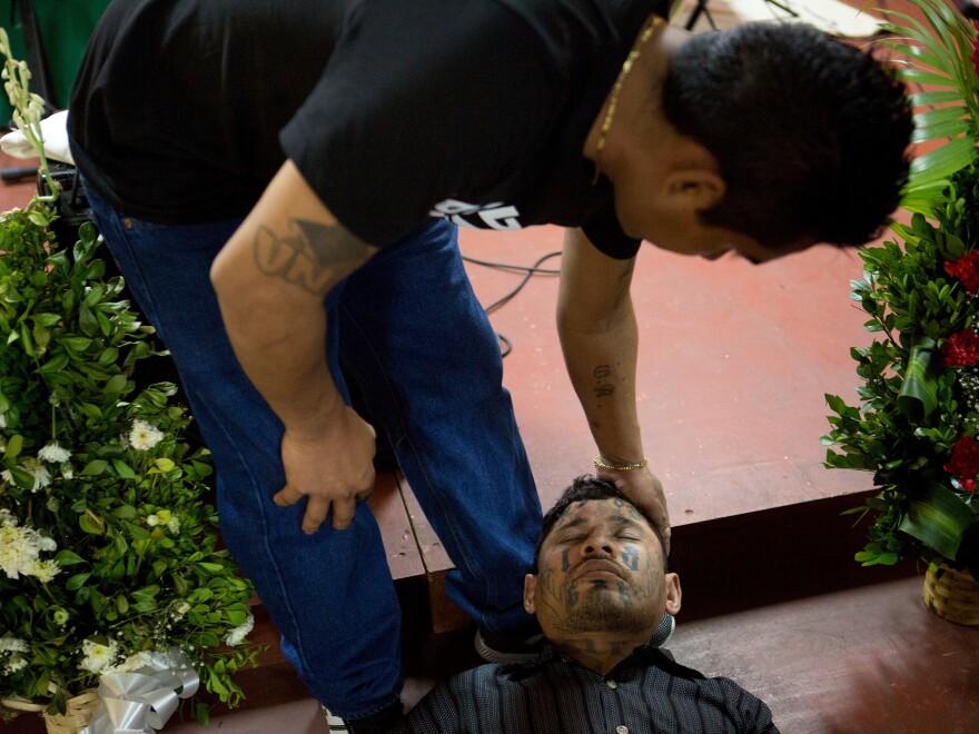 Carlos Montano, an ex-gang member, faints during prayer at San Salvador's Eben-ezer church.