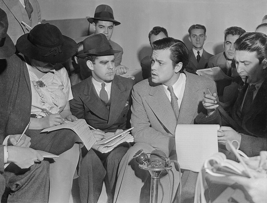 Photo of Orson Welles meeting with reporters in an effort to explain that no one connected with the War of the Worlds radio broadcast had any idea the show would cause panic.
