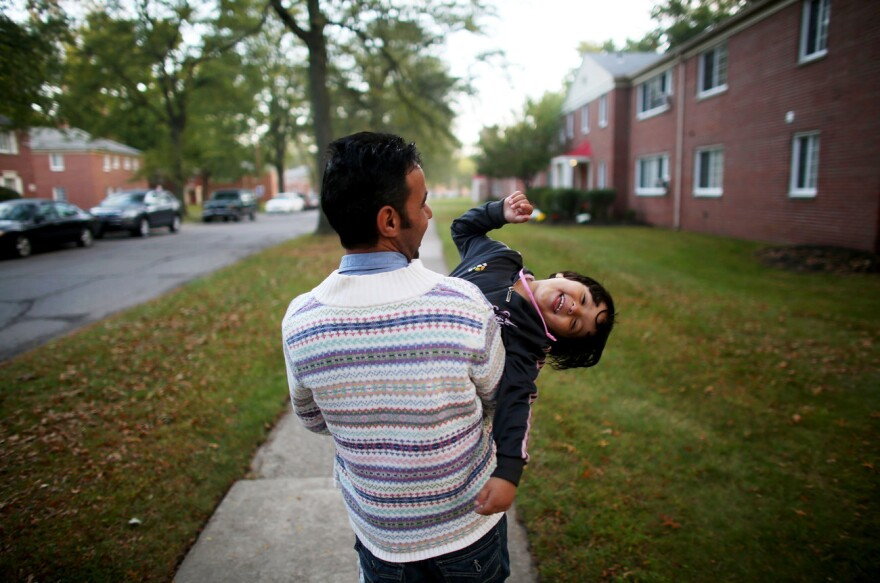 "Omar Al-Awad holds his daughter as they walk home in Toledo, Ohio, where they were recently resettled after fleeing Syria and living in a Jordanian refugee camp. <em>From the story ""<a href=""http://www.npr.org/2015/10/20/450221327/among-the-lucky-few-syrian-family-rebuilds-in-americas-heartland"" target=""_blank"">Among The Lucky Few: Syrian Family Rebuilds In America's Heartland</a>,"" 2015.</em>"