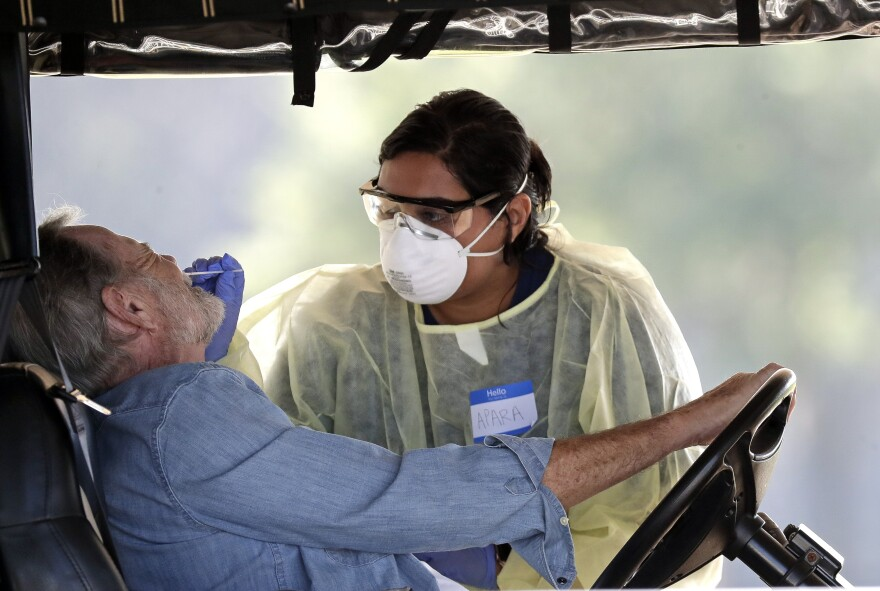 A resident gets tested for coronavirus at a mobile testing site Monday, March 23, 2020, in The Villages, Fla. The Villages, a retirement community, is one of the largest concentration of seniors in the U.S.